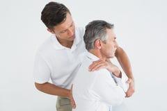 Manlig kiropraktor som undersöker den mogna mannen fotografering för bildbyråer