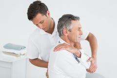 Manlig kiropraktor som undersöker den mogna mannen arkivfoton