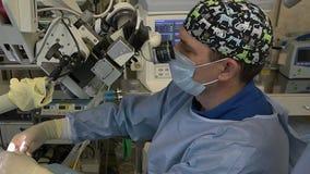 Manlig kirurg som gör mikroskopisk kirurgi på ENT organ genom att använda ett kirurgiskt mikroskop Innovativa teknologier i medic lager videofilmer