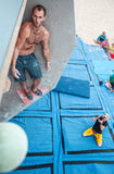 Manlig klättrare för hopp på den konstgjorda klättringväggen Royaltyfri Foto