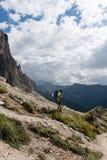 Manlig klättrare med ett sårat knä som fotvandrar ner en bergsida royaltyfria bilder