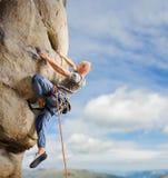 Manlig klättrare som klättrar den stora stenblocket i natur med repet arkivfoto