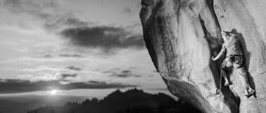 Manlig klättrare som klättrar den stora stenblocket i natur med repet royaltyfri bild