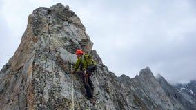 Manlig klättring för berghandbokledning på en utsatt granitkant i fjällängarna arkivfoton