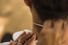 Manlig klient som får frisyr vid rakkniven royaltyfri fotografi