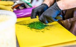 Manlig kock Cutting Dill på gult bräde royaltyfri foto