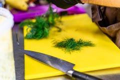 Manlig kock Cutting Dill på gult bräde royaltyfria bilder