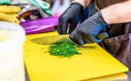 Manlig kock Cutting Dill på gult bräde arkivbilder