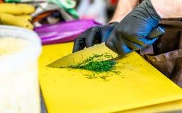 Manlig kock Cutting Dill på gult bräde arkivbild