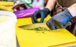Manlig kock Cutting Dill på gult bräde royaltyfria foton