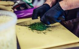 Manlig kock Cutting Dill på gult bräde i svarta handskar arkivbild