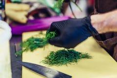 Manlig kock Cutting Dill på gult bräde i svarta handskar arkivfoton