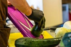 Manlig kock Cutting Eggplant i köket royaltyfria bilder