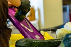 Manlig kock Cutting Eggplant i köket arkivfoto