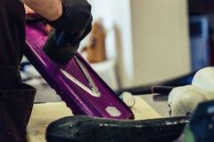 Manlig kock Cutting Eggplant i köket - med handsken på hans hand, begrepp av den hårda funktionsdugliga personen och hygienen i fotografering för bildbyråer