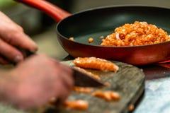 Manlig kock Cutting Fresh Salmon på träbrädet i Foregren fotografering för bildbyråer