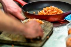 Manlig kock Cutting Fresh Salmon på träbrädet i Foregren royaltyfria foton