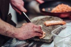 Manlig kock Cutting Fresh Salmon på träbrädet med den suddiga pannan i en bakgrund royaltyfria foton