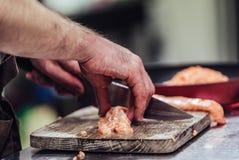 Manlig kock Cutting Fresh Salmon på träbrädet med den suddiga pannan i en bakgrund royaltyfri fotografi