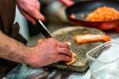 Manlig kock Cutting Fresh Salmon på träbrädet med gjort suddig arkivbild