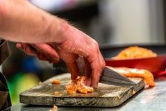 Manlig kock Cutting Fresh Salmon på träbrädet med gjort suddig arkivbilder
