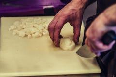 Manlig kock Cutting Potatoes på det gula brädet - ingredienser för sallader fotografering för bildbyråer