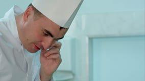 Manlig kock i vit enhetlig matlagning och samtal på telefonen stock video
