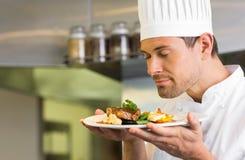 Manlig kock med stängda ögon lukta mat arkivbilder