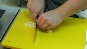 Manlig kock` s räcker att hugga av vitlök på ett specialt bräde lager videofilmer