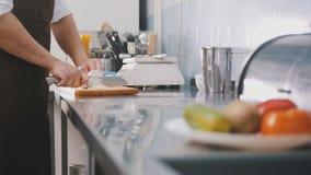 Manlig kock som förbereder sallad i kommersiellt kök - snitt löken Arkivbild