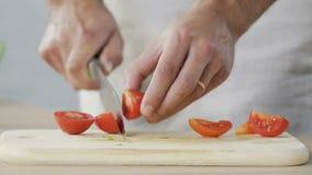 Manlig kock som klipper exakt tomater i kök och tillfogar den till maträtten som lagar mat stock video