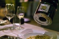 Manlig kock som kryddar pasta med peppar i en restaurang arkivfoto