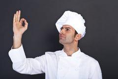 Manlig kock som kysser fingrar mot grå bakgrund Royaltyfria Bilder