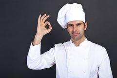 Manlig kock som kysser fingrar mot grå bakgrund Royaltyfri Foto