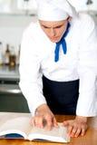 Manlig kock som ser till att laga mat handboken royaltyfri fotografi