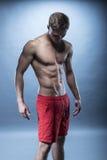 Manlig konditionmodell som bär röda kortslutningar Arkivfoto