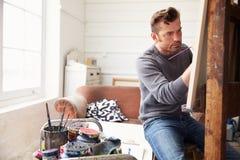 Manlig konstnär Working On Painting i studio fotografering för bildbyråer