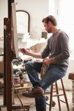 Manlig konstnär Working On Painting i studio royaltyfri bild