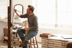 Manlig konstnär Working On Painting i studio arkivfoton