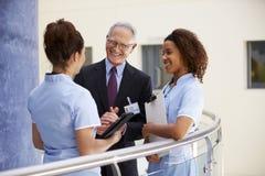 Manlig konsulent Meeting With Nurses som använder den Digital minnestavlan arkivfoton