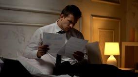 Manlig kontorist som sent förbereder rapporten på natten som jämför inkomst av företaget, diagram fotografering för bildbyråer