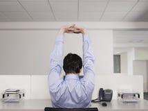 Manlig kontorsarbetare som sträcker på skrivbordet Arkivbilder