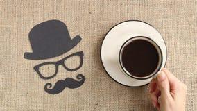 Manlig konturmodell med mustaschen, exponeringsglas och hatten med koppen kaffe på säckvävbakgrunden