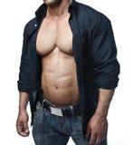 Manlig kroppsbyggare i jeans och den öppna skjortan som avslöjer pecs och abs Royaltyfri Foto