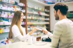 Manlig kund för erfaren apotekarerådgivning i apotek royaltyfria foton