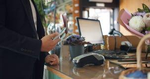 Manlig kund som betalar med smartphonen som tar därefter blommor från blomsterhandlare i lager arkivfilmer