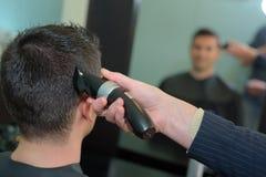 Manlig kund som har frisyr med nagelsax Royaltyfria Bilder