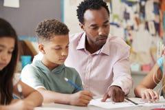 Manlig lärare som arbetar med skolpojken på skrivbordet, slut upp royaltyfria bilder