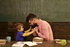 Manlig lärare som ger förklaringar till den lilla ungen Handleda, och hans lilla student har konversation om uppförande man in arkivfoton