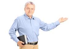 Manlig lärare som rymmer en bok och gör en gest med hans hand Royaltyfri Foto